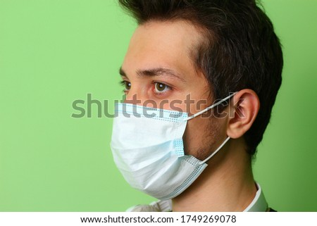 Close-up face of a young man in a surgical medical mask #1749269078