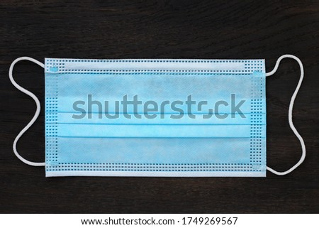 Medical surgical mask as the main symbol of covid-19 on a wooden background. #1749269567