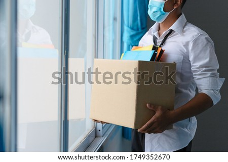 Asian unemployed person holds the document box by the window in hope, Unemployment in the Covid Virus Crisis 19. Business Failure Crisis was laid off from unemployment.  Royalty-Free Stock Photo #1749352670