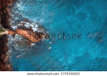 Aerial top view of cliff, surfers and turquoise transparent water  #1749360602