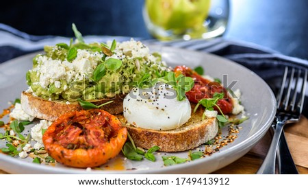 Avocado Toast featuring smashed avocado, grilled tomatoes, boiled egg on sourdough toast Royalty-Free Stock Photo #1749413912