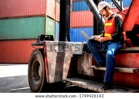 Industrial worker working at cargo freight logistic warehouse for import export, foreman use computer for online internet communication , Import and export business. #1749426143