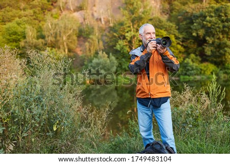 Senior photographer as a landscape photographer while photographing in nature