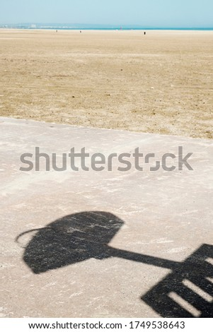 the shadow of a basketball backboard on the concrete floor of an outdoors basketball court on the beach, with the sea in the background