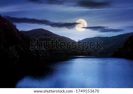 tarnita lake in romania at night. beautiful nature scenery in autumn in full moon light. gorgeous sky with glowing clouds Royalty-Free Stock Photo #1749553670
