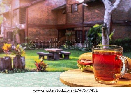 glass cup with tea and a sandwich, in front of a country house, concept breakfast outdoors, buy your house, horizontal