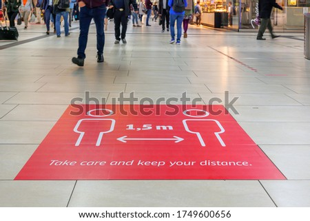 """Selected focus low angle view at """" Keep your distance"""", on red rectangular caution sign on the floor inside Main Train Station in Germany during Social Distancing by epidemic of COVID-19."""