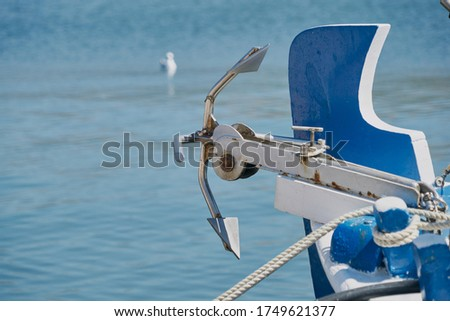 A picture of a boat with an anchor against a blue ocean at daytime