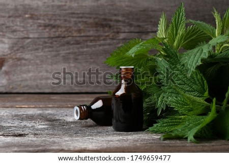 Essential oil and fresh green nettle leaves on  wooden background, medical concept about benefits of medicinal herbs, herbal medicine, natural cosmetics. #1749659477