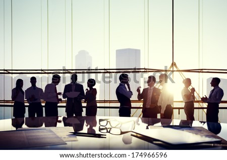 Group of Business People Discussing at Sunset Reflected Onto Table with Documents. #174966596