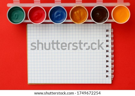 A blank sheet of checkered Notepad and a pen . Place for an inscription or text . Mockup with copy space. Blurred paint cans in the frame #1749672254