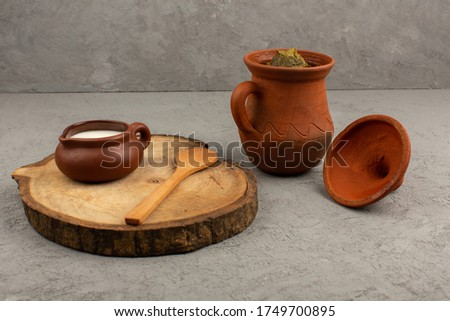 a front view brown pots designed with dolma and yogurt on the grey floor #1749700895