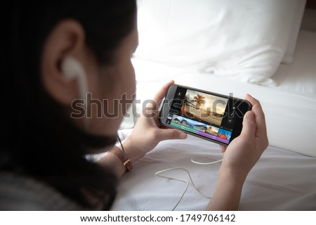 Mobile video editng application concept.Female holding mobile phone and wearing ear phone