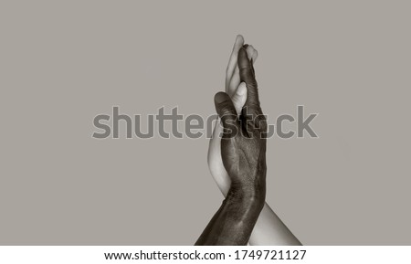 A black-and-white photograph in which black male and white female hands touch palms, intertwining. The concept of interracial friendship and respect. Copy of the space, gray isolated background