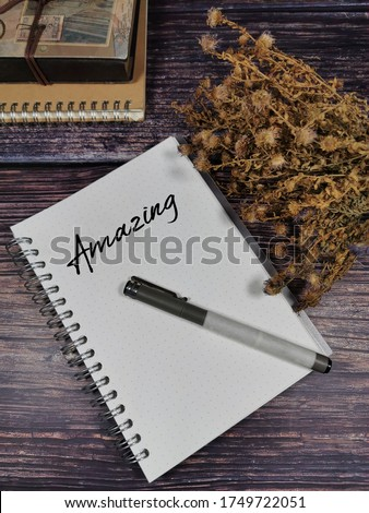 Amazing word on note book over wooden background.