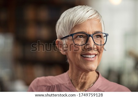 Portrait of smiling mature woman with spectacles in library looking away. Senior librarian standing in reading hall and thinking. Old beautiful lecturer contemplating. Future and vision concept. #1749759128