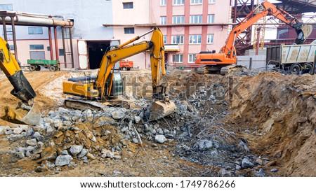 Powerful excavators dismantle concrete. Construction site. Dismantling of an industrial building. The destruction of reinforced concrete. Royalty-Free Stock Photo #1749786266