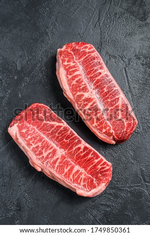 Raw top blade steak dry-aged. Black background. Top view Royalty-Free Stock Photo #1749850361