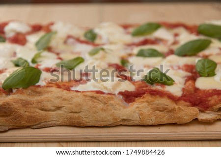 Close up on italian pinsa, a kind of pizza, resting on a restaurant table top. Royalty-Free Stock Photo #1749884426