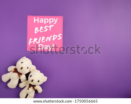 Friendship Celebration Concept - Happy best friends day text written on notepaper with teddies background. Stock photo