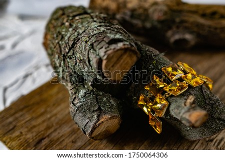 Beautiful and fashionable women's jewelry, elegant large yellow stones on a gold base, square shape, hanging on the bark and wooden natural snags Royalty-Free Stock Photo #1750064306
