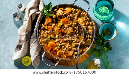banner of Black-eyed Pea Vegan Chili in a metal pan on a wooden stand on a blue background #1750167080