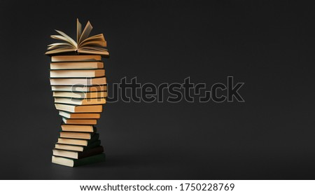 High books stack with one open on black background. Creative concept banner with old books. #1750228769