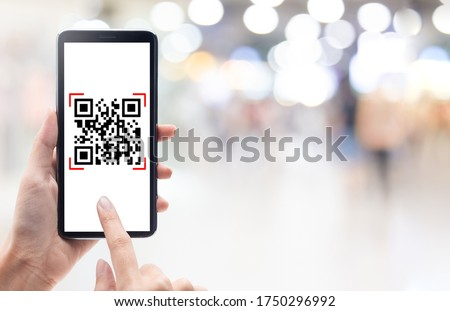 Hand using mobile smart phone scan Qr code on shopping mall background. Barcode reader, Qr code payment, Cashless technology, Digital money concept.