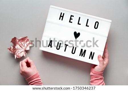 Lightbox with text Hello Autumn and heart on silver grey paper background. Flat lay with female hands that hold dry sycamore leaf pink metallic and the lightbox.