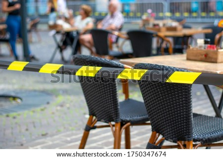 Terraces in city open again. Barrier tape on a terrace ensures that safe social distance can be kept between tables during coronavirus. Restaurant following rules of social distancing during covid-19 #1750347674