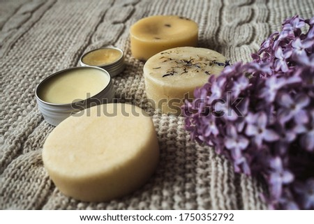 Eco-friendly unpacked homemade cosmetics. Solid shampoo, homemade soap, hair conditioner, hand cream and handmade lip balm in an aluminum jar lie on a knitted woolen beige plaid near by lilac branch. Royalty-Free Stock Photo #1750352792