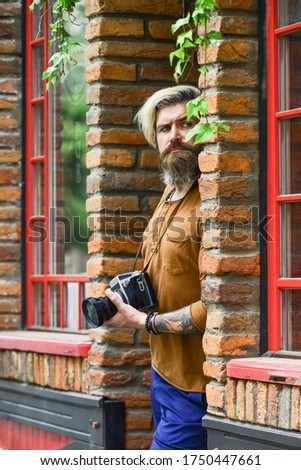 looking for someone. brutal man traveler with retro camera. photography in modern life. travel tips. professional photographer use camera. bearded man hipster take photo. photo shooting outdoor.