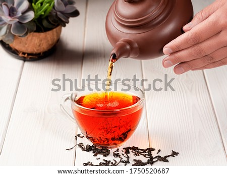 The process of brewing tea, tea ceremony. From a clay teapot, red tea is poured into a glass cup. Freshly brewed black tea, warm soft light, white wooden background, close-up. #1750520687