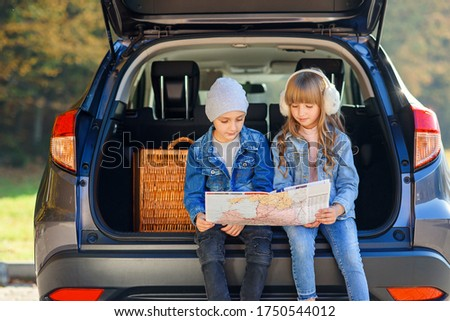 Cute stylish boy and pretty 10-s girl looking at the road map while sitting in the auto's trunk and discussing right direction to their family trip. Family vacation trip by car. Royalty-Free Stock Photo #1750544012