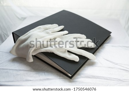Film photography album for negative storing. White cotton archival gloves in the background. Different size negatives in special envelopes. #1750546076