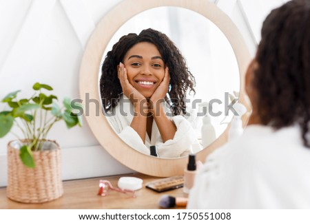 Self-Care. Beautiful African American Woman In Bathrobe Ready To Apply Makeup, Reflecting In Mirror Of Toilette Dresser Table, Looking At Camera #1750551008