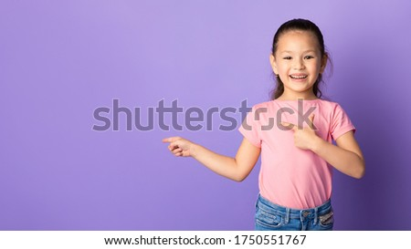 Look There. Smiling asian girl pointing her fingers at copyspace for your text or logo, pastel purple studio wall, banner