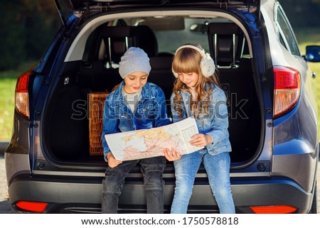 Cute stylish boy and pretty 10-s girl looking at the road map while sitting in the auto's trunk and discussing right direction to their family trip. Family vacation trip by car. Royalty-Free Stock Photo #1750578818