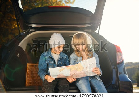 Stylish 12-s brother and his beautiful caucasian sister in denim clothes looking the road map in detail to choose right direction for their family trip. Family vacation trip by car. Royalty-Free Stock Photo #1750578821
