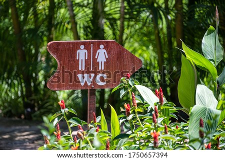 Vertical view of wooden sign of toilet give direction to WC in a tropical garden, Vietnam, close up