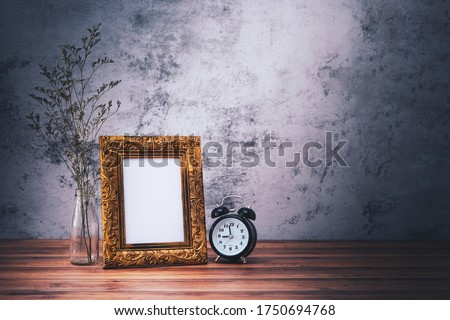 Picture frame and flowers and clock on wooden table. Poster product design styled