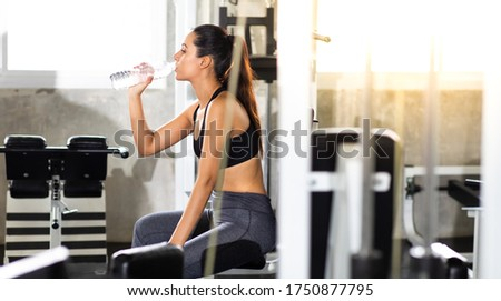 Female athlete taking rest and drinking woter after exercising at gym. Fitness Healthy lifestye and workout at gym concept.