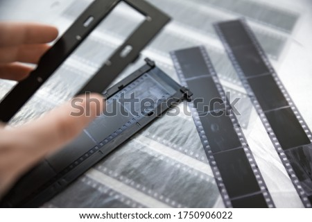 Film photography special envelope slips for negative storage. 35mm and medium format photography. Holding a film strip, putting it inside a scanner frame, preparing for scanning.