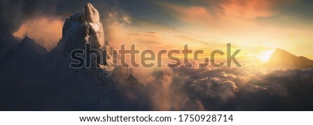 Beautiful aerial landscape of mountain peak at sunset above the clouds - panoramic Royalty-Free Stock Photo #1750928714