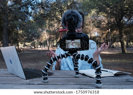 Young woman and youtuber vlogging or recording a video vlog in a park. She's sitting on a wooden bench in a park and uses her laptop to read what she's saying.