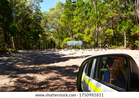 Close up view of side mirror on suv taking picture of dirt road on Fraser Island, Queensland, Australia; sign give distance to destination