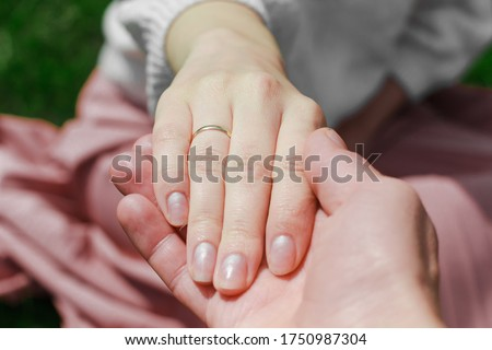 Man holding woman's hand with wedding ring on finger close up. Bride and groom. Forever together, young couple in love. Concept of marriage, wedding, love symbol, relationship goals, active lifestyle.