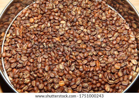 A picture of Just roasted dark brown coffee beans.