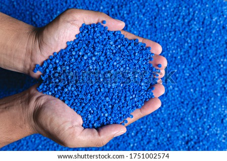 Blue plastic grain, plastic polymer granules,hand hold Polymer pellets, Raw materials for making water pipes, Plastics from petrochemicals and compound extrusion, resin from plant polyethylene. Royalty-Free Stock Photo #1751002574