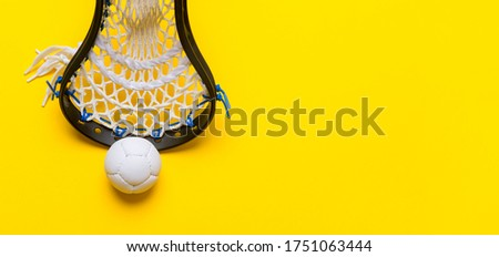 Close-Up Of Lacrosse Equipment On Yellow Background. Lacross is a team sport